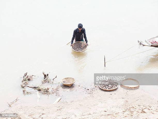 SHYLETH JAFLONG DHAKA BANGLADESH A worker collects stone from the river at Jaflong in Shyleth Bangladesh