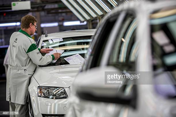 A worker completes a quality control check on a finished Skoda Octavia automobile on the production line at Volkswagen AG's Skoda Auto AS...