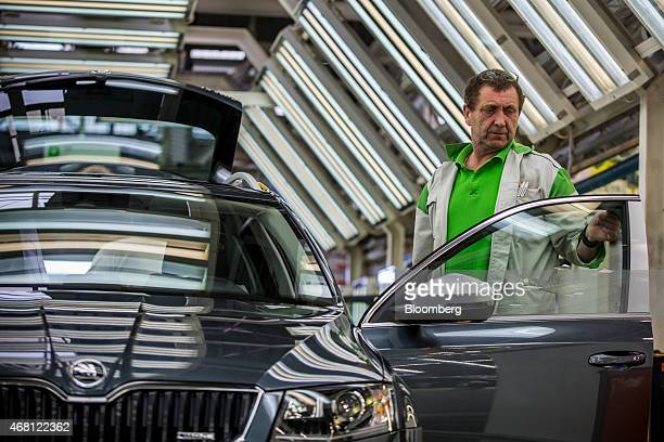 A worker completes a quality control inspection on the door of a finished Skoda Octavia automobile on the production line at Volkswagen AG's Skoda...
