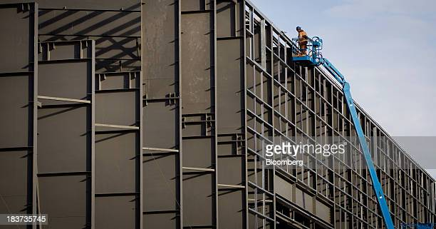 A worker continues construction in a cherry picker on a building to be used for ship manufacturing at the Seaspan Vancouver Shipyard in North...