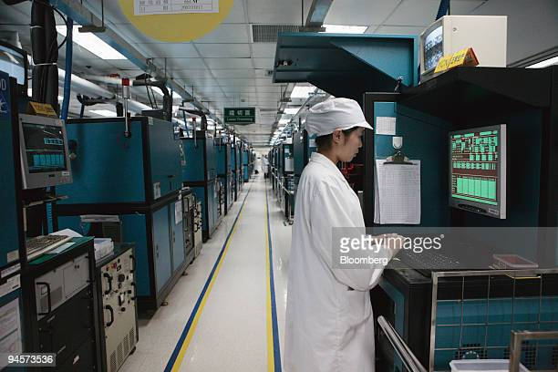A worker control a laser trimming machine at a chip resistors production line of Yageo in Suzhou China on Monday October 29 2007