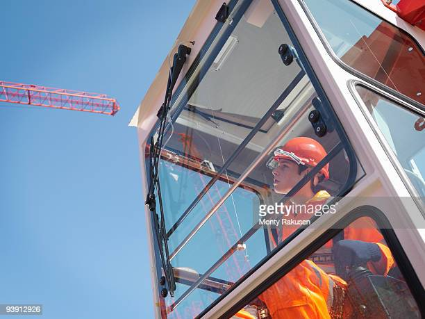 worker controlling crane from cabin - crane construction machinery stock pictures, royalty-free photos & images