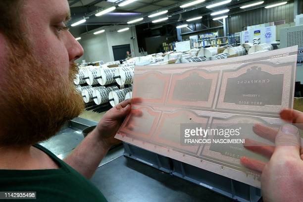 Worker controls labels of champagne bottle at the Billet printing company in Damery, eastern France, on April 16, 2019. - Using a combination of...