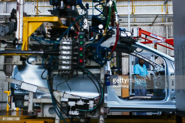 A worker controls machinery to work on the body of a VW Polo automobiles on the production line at the Volkswagen AG plant in Uitenhage South Africa...