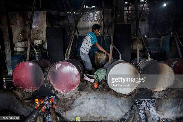 A worker controls the heat of boiler drums during the distillation process of ethanol alcohol at Bekonang village on February 9 2016 in Sukoharjo...