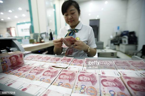 A worker counts Chinese currency Renminbi at a bank in Hauibei east China's Anhui Province Aug 26 2015 China's yuan fell against the dollar on...