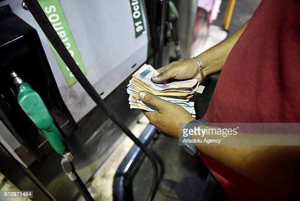 A worker counts money while putting gas to a vehicle in Caracas Venezuela on February 17 2016 Venezuela's President Nicolas Maduro said Wednesday he...