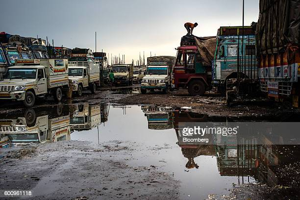 A worker covers a truck with tarpaulin in a waterlogged truck stop at the Bara Bazar Market in Shillong Meghalaya India on Tuesday Aug 16 2016 Two...