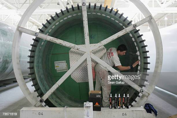 A worker covers bolt heads in a 45 meter long wind turbine blade at the Nordex wind turbine factory March 12 2007 in Roctock Germany Nordex has seen...