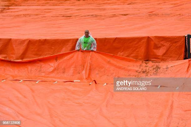 TOPSHOT A worker covers the central court as tennis matches are suspended due to persistent rain during the ATP Tennis Open tournament on May 15 2018...