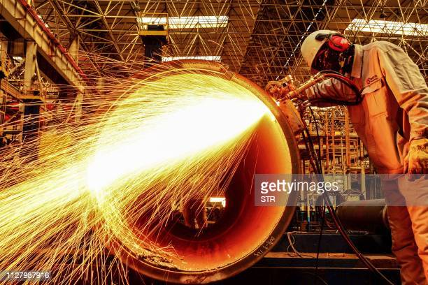 A worker cuts an oil pipe at a factory in Qingdao in China's eastern Shandong province on February 28 2019 China's manufacturing activity shrunk for...