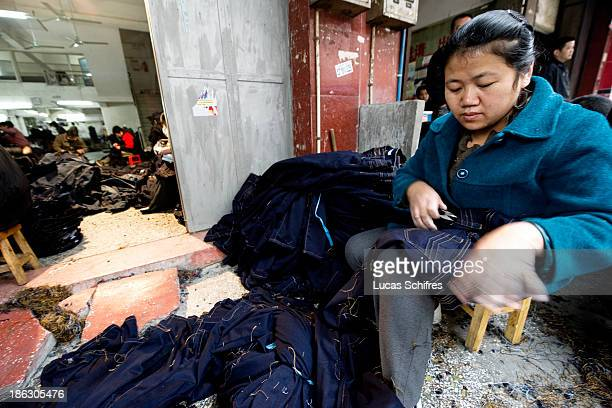 A worker cuts by hand remaining strings left by the sewing machine on newly manufactured blue jeans in a little workshop by the street on February 10...
