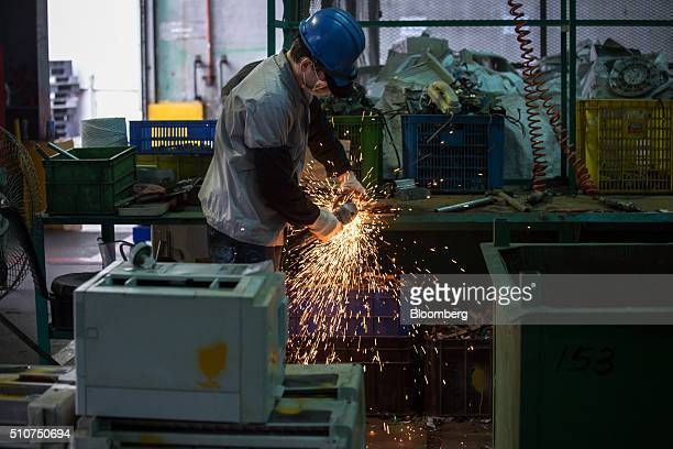 A worker cuts electronic parts at the Super Dragon Technology Inc ewaste processing facility in Taoyuan Taiwan on Wednesday Jan 13 2016 Super Dragon...