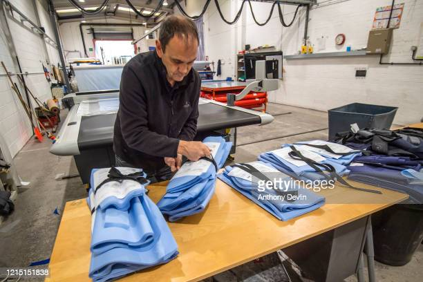 Worker cuts fabric for NHS uniforms onto a measuring machine as staff at Tibard begin work on a new order of 20,000 nurses uniforms at their factory...