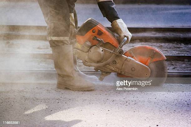Worker cuts into a road with a circular saw to make repairs