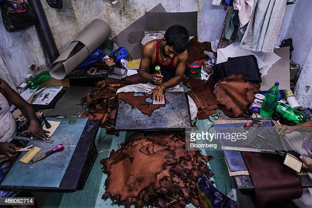 A worker cuts leather pieces from a hide for a wallet at a leather workshop in the Dharavi slum area of Mumbai India on Saturday Aug 29 2015 India's...