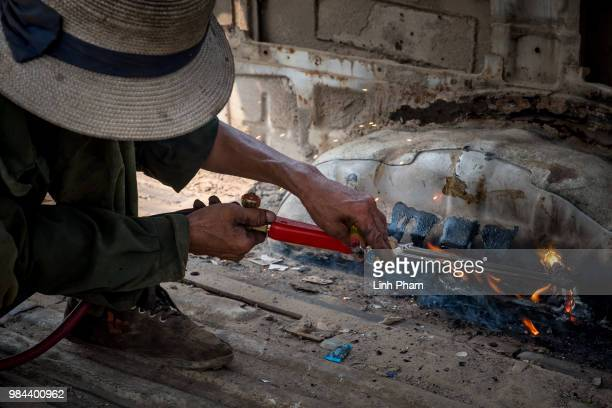 A worker cuts out an old van on the main road of Te Lo village on June 7 2018 in Te Lo Village Yen Lac District Vinh Phuc Province Vietnam Vietnam...