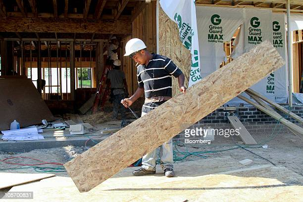 A worker cuts plywood boards for a new home under construction in Cary North Carolina US on Tuesday Oct 19 2010 Builders in the US unexpectedly began...