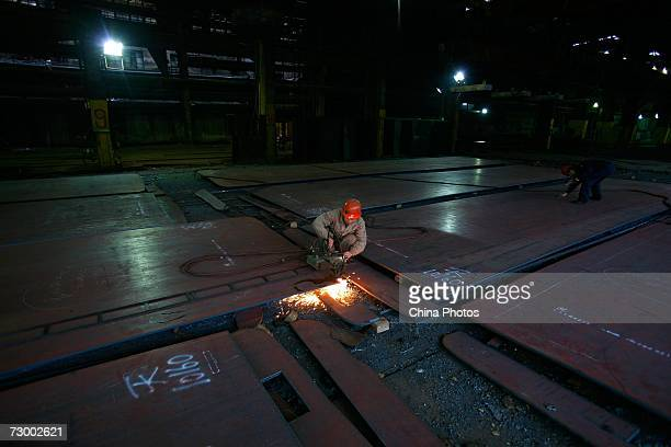 A worker cuts steel plates at a Shanghai Baosteel Group factory January 15 2007 in Shanghai China According to state media Baosteel is preparing for...