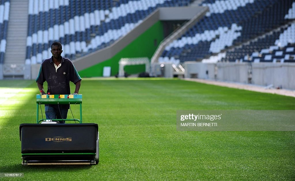 A worker cuts the grass of the field of the Mbombela Stadium, in Nelspruit on June 5, 2010 in preparation for the start of the FIFA 2010 World Cup. Chile and Honduras will play their first match of the tournament here on June 16. AFP PHOTO / Martin BERNETTI