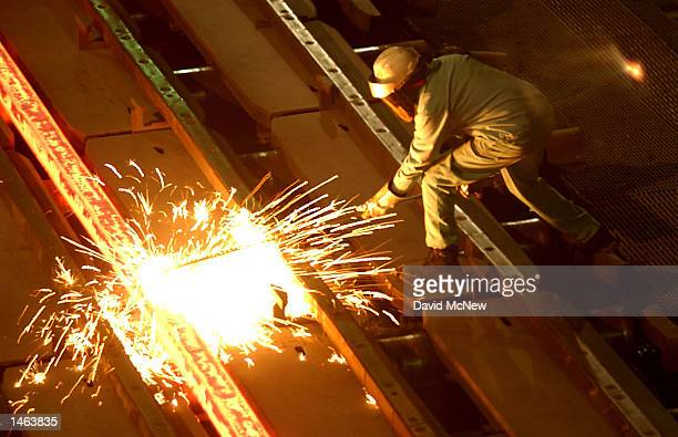 A worker cuts through a glowing 2000 degrees Fahrenheit billet at the TAMCO steel mini mill on October 4 2002 in Rancho Cucamonga California TAMCO...