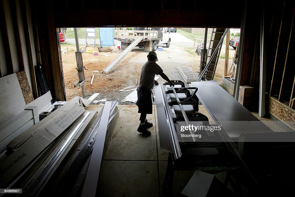 A worker cuts vinyl siding for a Centex home under