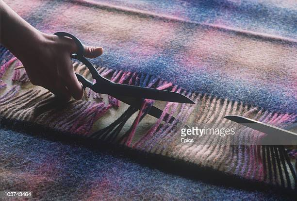 Worker cuts wool with a pair of large cutting scissors at Foxford Woollen mill, which has been producing the famous Foxford blankets since 1892,...