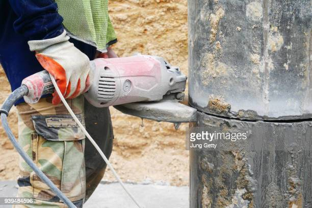 Worker cutting concrete pile column by electric cutting machine. Worker with high shear grinder cut and mill cement