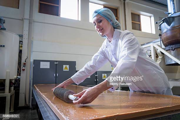 Worker cutting confectionery fudge in chocolate factory
