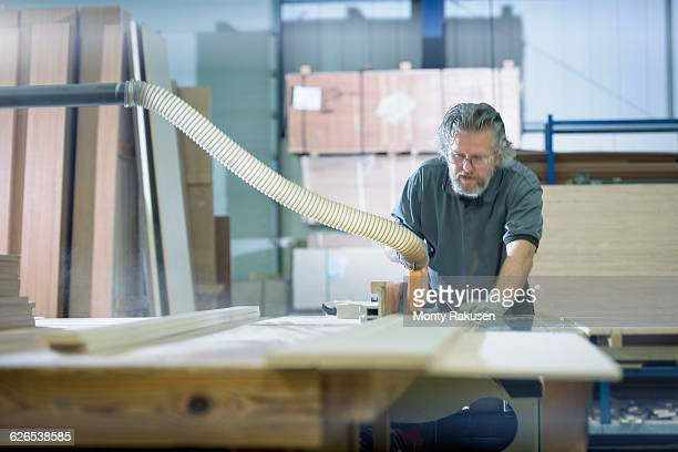 Worker cutting timber in motorhome factory