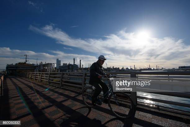 A worker cycles along a bridge in the Keihin industrial area of Kawasaki Kanagawa Prefecture Japan on Tuesday Dec 12 2017 The Bank of Japan will...