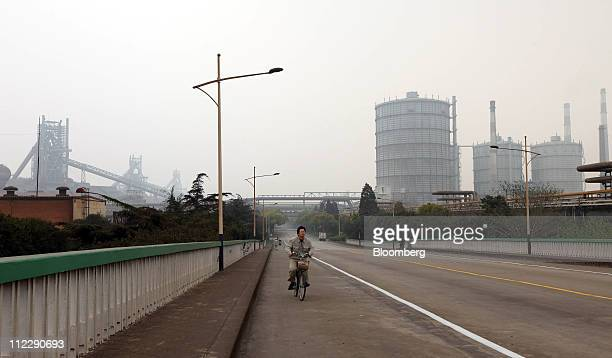 A worker cycles through the Baosteel Group Corp campus in Shanghai China on Friday April 15 2011 Baosteel Group is the supplier of half the sheets...
