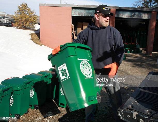 DPW worker Dave Doucette loads curbside recycling bins onto truck as residents gathered at a town garage to distribute curbside composting bins to...