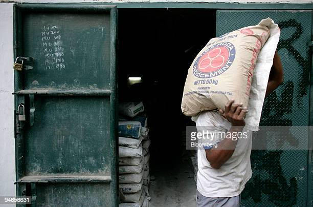 A worker delivers bags of PT Indocement Tunggal Prakarsa cement to a shop in Jakarta Indonesia Wednesday April 4 2007 PT Indocement Tunggal Prakarsa...