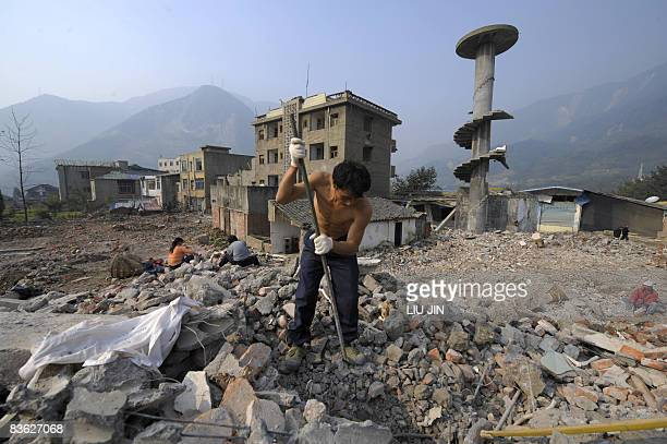 J SAIGET A worker demolishes the ruins of collapsed houses in Leigu township of Beichuan county in China's southwestern province of Sichuan on...