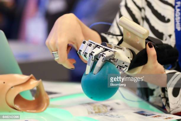 A worker demonstrates a prosthetic hand which mimicks her hand gestures on the Graphene Flagship stand on the second day of Mobile World Congress in...