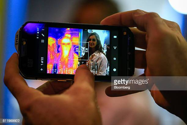 A worker demonstrates the thermal imaging camera function on the Cat S60 smartphone manufactured by Caterpillar Inc at the Mobile World Congress in...