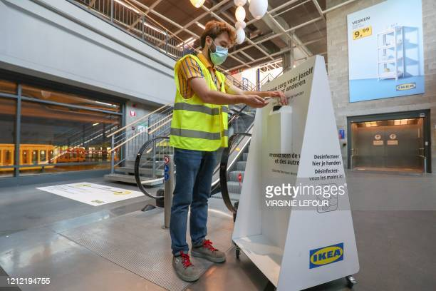 A worker demonstrates the use of a bottle of hand sanitiser in the furniture department of an IKEA store in Anderlecht District of Brussels on May 8...