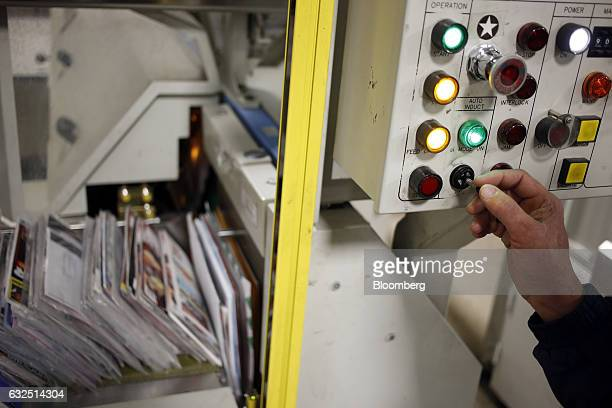 A worker demonstrates the use of an automated mail sorting machine at the United States Postal Service sorting center in Louisville Kentucky US on...