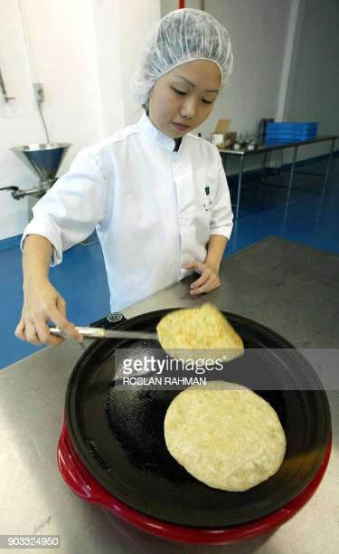 A worker demonstrates the way of cooking instant Indian pancakes at Tee Yih Jia food manufacturing in Singapore 11 June 2002 As Singapore searches...