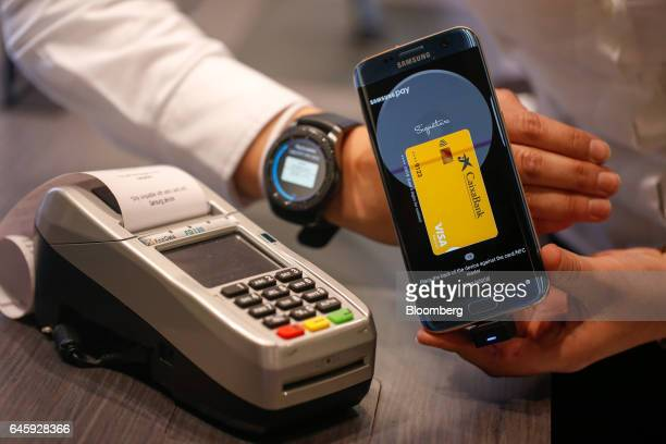 A worker demonstrates wireless payment using the Samsung Pay app on a Galaxy smartphone and a Gear smartwatch manufactured by Samsung Electronics Co...
