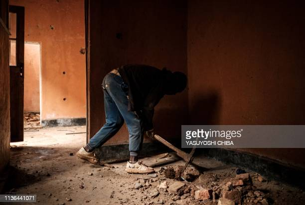 A worker digs a floor with a pickax to locate a pit which was used as mass grave during 1994 Rwandan genocide and hidden under a house is seen in...