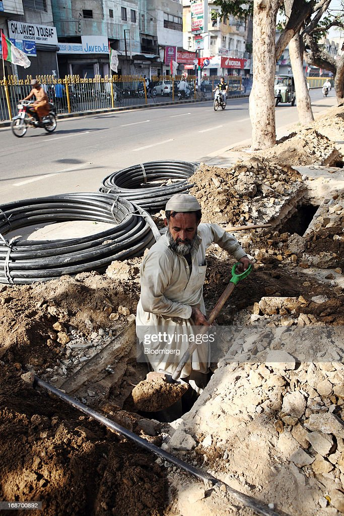 A worker digs a hole for a high speed telecommunications line in Karachi, Pakistan, on Monday, May 13, 2013. Nawaz Sharif was headed for a record third term as prime minister of Pakistan as unofficial results from a landmark election gave him the convincing win he sought to tackle a slumping economy and growing militancy. Photographer: Asim Hafeez/Bloomberg via Getty Images