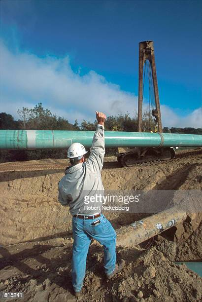 A worker directs a sideboom operator to lay a new 42inch piece of pipe into a trench with an existing 26inch white pipe October 3 2000 in Howell...