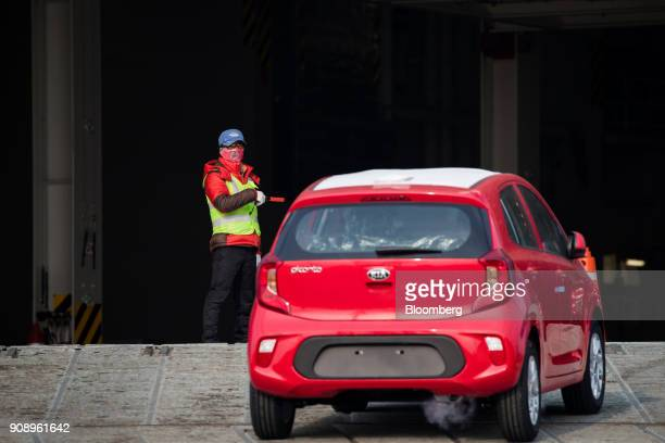A worker directs the driver of a Kia Motors Corp vehicle bound for export into the Hyundai Glovis Co Glovis Safety rollon/rolloff vehicles carrier...