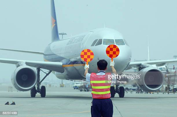 A worker directs the first airliner of the United Eagle Airlines which arrives at the Shuangliu Airport from Macau on July 14 2005 in Chengdu of...