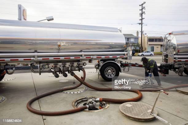 A worker disconnects hoses after delivering gasoline from a fuel tanker truck at a Royal Dutch Shell Plc gas station in Redondo Beach California US...