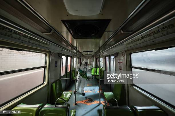 A worker disinfects a metro train car at Coordinación de Mantenimiento Mayor Ticoman Coach Yard on March 18 2020 in Mexico City Mexico The Mexico...