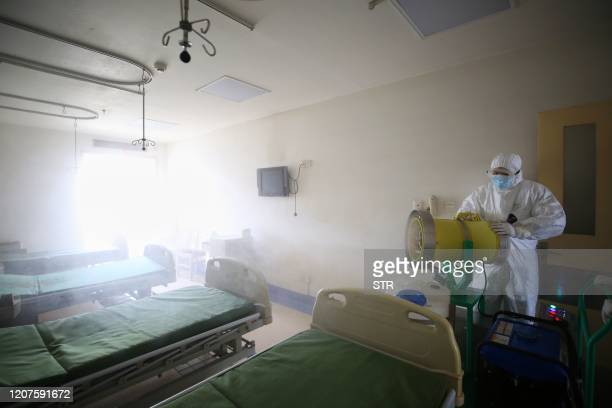TOPSHOT A worker disinfects a room at the Red Cross hospital in Wuhan in China's central Hubei province on March 18 2020 The hospital which has been...