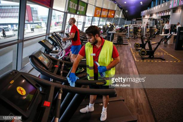 A worker disinfects a treadmill in the gym at London Aquatics Centre on July 25 2020 in London England After further easing of the United Kingdom's...